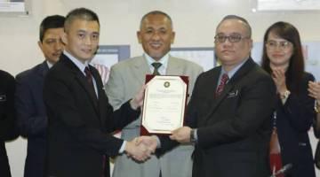 Razim tengah menyaksikan pertukaran dokumen serah terima tugas antara Zulhairy (kanan) dan Chang Ching.