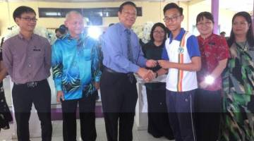 Dr Teo menyampaikan kupon kepada seorang pelajar SMKDP disaksikan guru dan ahli PIBG.
