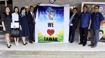 FESTIVAL: Pengurus Syarikat Top Green Tech Sdn Bhd (TGT) Albert J.Kok (empat kiri) menyerahkan banner kepada Alijus selepas pelancaran pemasangan Lightbox (Iklan elektronik) Majlis Perbandaran Tawau (MPT) semalam. — Gambar Bernama