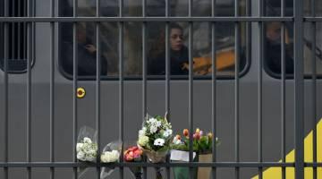 BUNGA: Seorang penumpang (tengah) dalam sebuah trem melihat bunga yang dipamerkan dekat lokasi serangan maut di 24 Oktoberplein di Utrecht, pada Selasa. — Gambar AFP