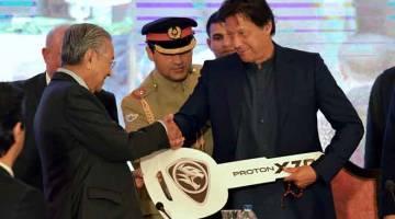SIMBOLIK: Tun Dr Mahathir (kiri) menyerahkan replika kunci kenderaan Proton X70 kepada rakan sejawatannya dari Pakistan Imran Khan pada upacara simbolik pecah tanah bagi kilang pemasangan pembuatan pengeluar kereta nasional Malaysia, Proton, di negara itu pada Jumaat. — Gambar Bernama