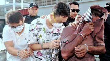 PERTUDUHAN: Tiga suspek kes pencemaran kimia di Sungai Kim Kim diiringi anggota polis tiba di Mahkamah Sesyen Johor Bahru bagi menghadapi pertuduhan, semalam. — Gambar Bernama