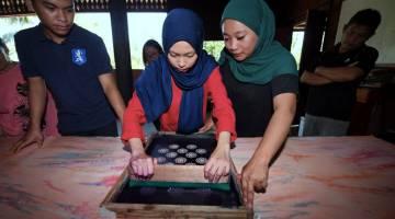 CETAKAN BATIK: Teknik cetakan Batik Linut dilakukan mengikut motif yang dihasilkan di Kampung Telian Tengah Mukah. — Gambar Bernama