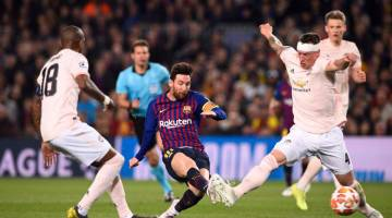 AKSI LUAR BIASA: Messi (tengah) melepaskan rembatan melepasi kawalan pemain United sebelum menjaringkan gol ketiga Barca pada perlawanan di Nou Camp, Barcelona Rabu lepas. — Gambar AFP