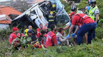 KEMALANGAN DAHSYAT: Anggota bomba membantu mangsa bas pelancongan yang mengalami kemalangan pada Rabu di Caniço, di Pulau Madeira, Portugal. — Gambar AFP