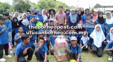 UNTUK ALBUM: Ali (tengah) merakamkan kenangan bersama anggota Rumah Sukan yang memenangi salah satu acara pada kejohanan tersebut.