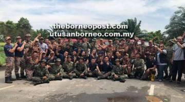 BERSEMANGAT: Anggota bomba, tentera dan Radio Amatur Miri merakamkan gambar kenangan semasa operasi bersama bagi menangani asap tebal kesan kebakaran di kawasan berdekatan Curtin Malaysia, semalam.