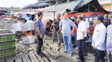 MOHAMADDIN bersama Mohd Ayub ketika melawat tapak pasar ayam.
