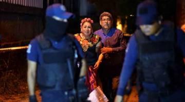 TERKEJUT: Sepasang warga emas cuba bertanyakan sesuatu kepada pegawai polis yang berkawal di tempat kejadian di mana penyerang bersenjata melepaskan tembaka di sebuah kelab malam di Minatitlan, Veracruz kelmarin. — Gambar Reuters