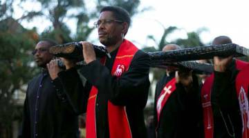 PERINGATAN: Para pemimpin gereja membawa sebuah salib besar semasa perarakan keagamaan sempena Good Friday di Durban, kelmarin. — Gambar Reuters