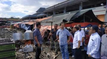 UZUR: Mohamaddin bersama Mohd Ayub melawat tapak pasar ayam hidup di Lahad Datu.