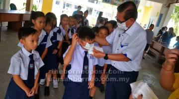 TUNJUK: Lee menunjukkan cara betul menggunakan topeng muka kepada murid-murid.