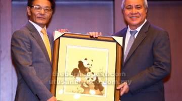TERUS KUKUH: Cheng menyerahkan cenderamata kepada Awang Tengah sebagai tanda penghargaan mengadiri Bengkel Ekonomi dan dan Taklimat Dasar Kerja Sama Antara China dan Sarawak.