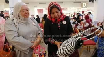 MENARIK: Arpah (kiri) dan Rosey melihat pameran kraf yang diadakan semasa pelancaran tersebut di sebuah pusat beli-belah di Miri semalam.