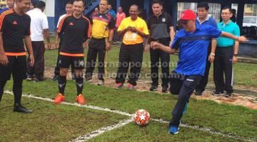 MULA: Martin menyepak bola untuk merasmikan pertandingan bola sepak Piala KPD pagi semalam.