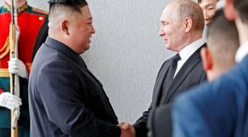 HUBUNGAN ERAT: Putin dan Kim berjabat tangan semasa pertemuan empat mata buat kali pertama antara kedua-dua pemimpin itu di Vladivostok, Rusia semalam. — Gambar Reuters