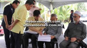BINCANG: Talib (dua kanan) mendengar penerangan daripada Lau Pit Hwa (kiri) mengenai projek yang telah dilaksanakan di Kuala Tatau.