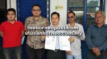 MOHON SIASAT: Abun Sui (tengah) menunjukkan salinan laporan polis dibuat beliau dan salinan artikel daripada Sarawak Report mengenai dakwaan terhadap pimpinan PRS.