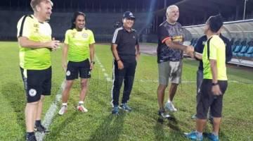 John (tiga kiri) bersalam dengan jurulatih, Edward Jamid Unting sambil disaksikan penasihat pasukan Sarawak, Lukas Kalang Laeng (tiga kiri) dan barisan jurulatih lain semasa sesi latihan malam kelmarin.