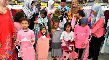 BANTUAN: Dr Nila Armila (tiga, kiri), bersama Najwah Halimah (dua, kiri) dan Zainal (tiga, kanan) memakaikan pakaian kepada anak-anak asnaf pada Program Bantuan Raya Anak-Anak Asnaf Parlimen Pulai di Mydin Mall Mutiara Rini semalam. — Gambar Bernama