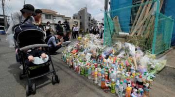 MENYAYAT HATI: Orang ramai berkunjung ke tempat kejadian di Kawasaki, semalam di mana seorang lelaki menikam 19 orang termasuk kanak-kanak. — Gambar AFP