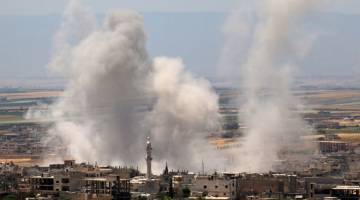 BERTERUSAN: Asap tebal berkepul susulan pengeboman oleh tentera Syria di bandar Khan Sheikhun, pinggir selatan wilayah Idlib semalam. — Gambar AFP