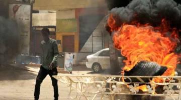 TEGANG: Penunjuk perasaan berjalan melintasi tayar terbakar berhampiran ibu pejabat tentera di Khartoum, Sudan kelmarin selepas pasukan keselamatan meleraikan tunjuk perasaan selama                        berminggu-minggu yang mengorbankan lebih 30 nyawa. — Gambar AFP
