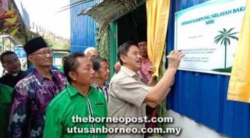 SUDAH RASMI: Ripin (kanan) menandatangani plak sempena perasmian Dewan Kampung Nelayan Kuala Bakam, Miri pagi semalam.
