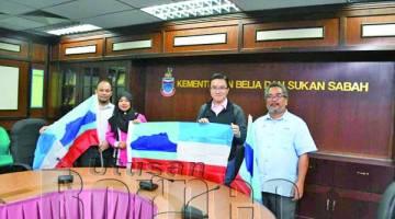 PHOONG menyerahkan bendera Sabah kepada Jumaidah semasa kunjungan hormat.