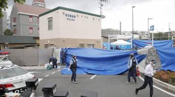 KECOH: Para pegawai polis menjalankan siasatan di tempat kejadian di hadapan balai polis di Suita, wilayah barat Osaka kelmarin dalam gambar serahan Kyodo. — Gambar Reuters