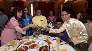 MESRA: Kok (kiri) menyampaikan sumbangan duit raya kepada warga Kementerian Industri Utama pada Majlis Ramah Mesra dan Sambutan Hari Raya Aidilfitri semalam. — Gambar Bernama