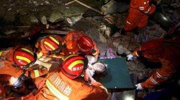 MUJUR SELAMAT: Anggota penyelamat mengangkat seorang wanita yang cedera ketika mereka mencari mangsa terselamat dalam runtuhan bangunan selepas gempa bumi melanda daerah Changning di Yibin, wilayah Sichuan, China semalam. — Gambar China Daily/Reuters