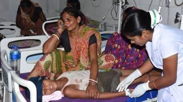 DEMAM TERUK: Gambar fail diambil pada 10 Jun lalu menunjukkan seorang wanita menangis di sebelah anaknya yang sedang menjalani rawatan disebabkan AES di hospital di Muzaffarpur, India. — Gambar AFP