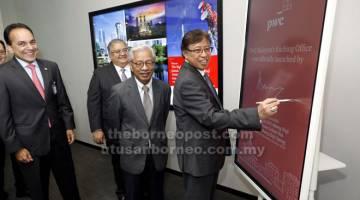 SIMBOLIK: Abang Johari menurunkan tandatangan di atas plak khas bagi merasmikan pejabat PwC di Kuching. Turut kelihatan (dari kiri) Sridharan, Masing dan Mohammad Faiz (belakang). — Gambar Chimon Upon