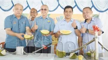 DARI kiri: Jamal, Rozman, Amir dan Jurijh memperlihatkan salah satu spesies durian Labuan berkualiti tinggi.