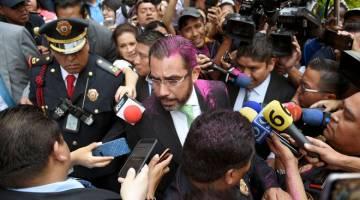 MENJADI MANGSA: Orta Martinez dengan rambut disembur merah jambu oleh seorang penunjuk perasaan, dikerumuni wartawan ketika cuba menenangkan protes mengecam polis di hadapan Kementerian Keselamatan Awam di Kota Mexico, kelmarin. — Gambar AFP