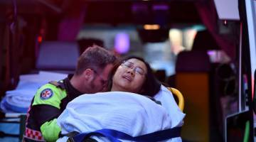 CEDERA: Seorang wanita yang dipercayai ditikam dari belakang diusung ke dalam ambulans ketika polis menyiasat tempat kejadian di Sydney, semalam. — Gambar Reuters