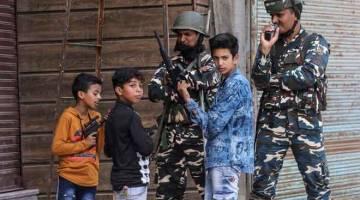 TETAP CERIA: Kanak-kanak bermain dengan pistol mainan di sebelah anggota tentera India             semasa perintah berkurung di wilayah Kashmir yang dikuasai India kelmarin. — Gambar Reuters
