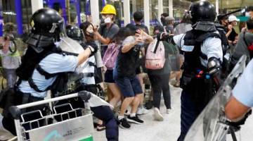 HURU-HARA: Polis menggunakan penyembur lada untuk menyuraikan penunjuk perasaan selepas rapat umum bertukar ganas di lapangan terbang Hong Kong, China kelmarin. — Gambar Reuters