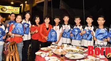 SERAH BEG: Susan (enam dari kiri) menyerahkan beg sekolah kepada pelajar WYU.