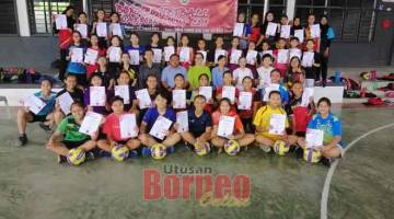 BERSEDIA: Mikar (empat kiri) merakam kenangan bersama peserta dan pegawai skuad bola jaring Sarawak pada kem latihan tersebut.
