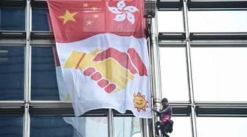 SERUAN KEDAMAIAN: Robert dilihat memasang 'kain rentang kedamaian' selepas memanjat menara pencakar langit Pusat Cheung Kong di Hong Kong, China semalam. — Gambar AFP
