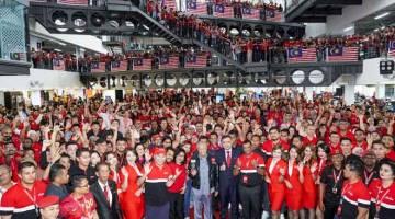 UNGKUP KENANG: Dr Mahathir (tengah) disempulang Loke begambar ungkup kenang enggau staf AirAsia maya program nya.