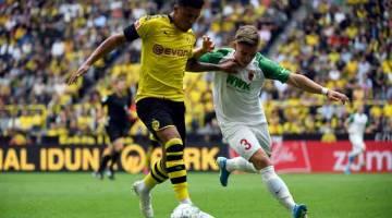 PRESTASI HEBAT: Sancho (kiri) mengawal bola ketika bersaing dengan pemain Augsburg pada perlawanan Bundesliga Jerman di Signal Iduna Park, Dortmund kelmarin. — Gambar AFP