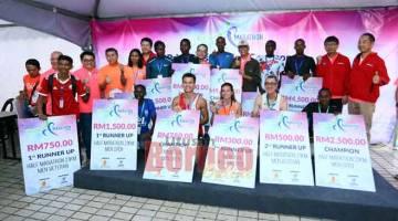 TAHNIAH: Pemenang-pemenang bersama Abang Wahap (lima kanan) dan tetamu lain pada majlis penyampaian hadiah Kuching Marathon 2019 semalam. — Gambar Muhammad Rais Sanusi