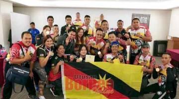 TERBAIK: Barisan 'puller' Sarawak bersama Matthew dan Louise (tengah) meraikan kejayaan setelah mencapai keputusan terbaik pada kejohanan gusti lengan kebangsaan, Sabtu lalu.