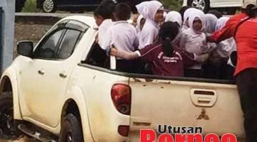 PRIHATIN: Murid-murid ini terpaksa menaiki kenderaan pacuan empat roda beramai-ramai akibat banjir kilat yang menimpa sekolah mereka.