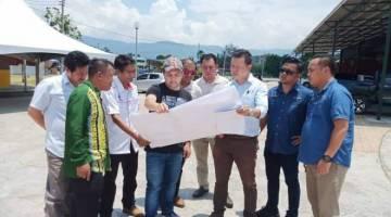TELITI: Jamawi (empat dari kiri) bersama pegawai kanan LPBB meninjau pelan pembinaan pekan baharu Kemabong.