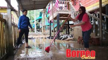GOTONG-ROYONG: Hasman dan isterinya bergotong-royong membersihkan kawasan halaman rumah mereka akibat kesan banjir.