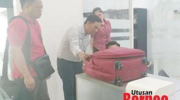 PERIKSA: Saibi (kiri) memerhati kakitangan syarikat penerbangan memeriksa begnya yang terkopek ketika membuat aduan.